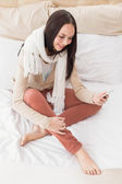 Pretty brunette sending a text on bed — Stock Photo