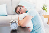 Bored man on the table beside alarm clock — Stock Photo