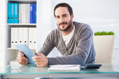 Casual smiling businessman using tablet and calculator — Stock Photo