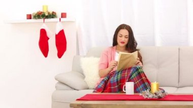 Pretty brunette relaxing on the couch at christmas time — Vídeo de Stock
