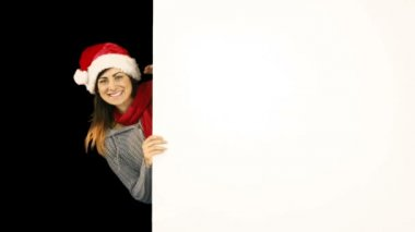 Beauty brunette in santa hat pointing white poster — Stock Video