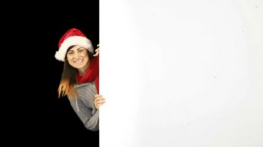 Beauty brunette in santa hat showing white poster — Stock Video