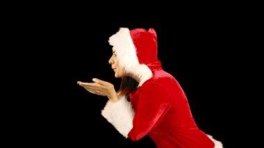 Pretty brunette in santa hat blowing over hands — Stock Video