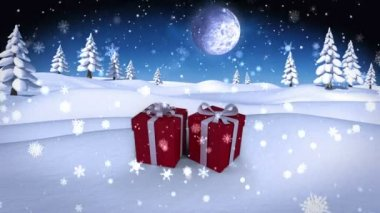 Snow falling on christmas presents in snowy landscape — Stock Video