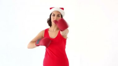 Fit festive brunette punching with boxing gloves in santa hat — Stock Video