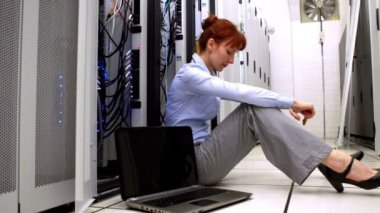 Stressed technician sitting on floor beside open server — Vídeo Stock