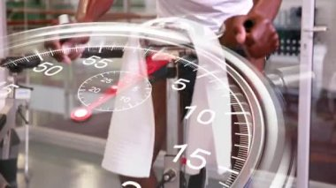 Stopwatch graphic over man using exercise bike — Wideo stockowe