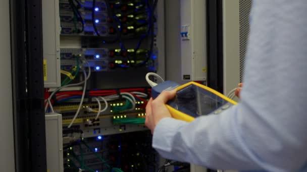 Technicien en utilisant l'analyseur de câble numérique sur serveur — Vidéo