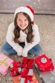 Festive little girl smiling at camera with gifts — Foto de Stock