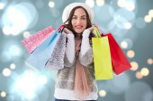 Composite image of brunette in winter clothes with shopping bags — Stock Photo