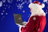 Santa Claus uses laptop — Stock Photo