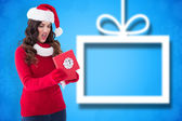 Composite image of disappointed brunette opening christmas gift — Stockfoto