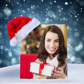 Smiling brunette holding gift on the couch — Stock fotografie