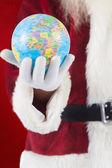 Santa has a globe in hand — Stock Photo