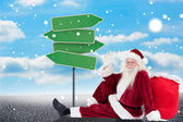 Santa sits leaned on his bag and waves — Foto de Stock