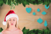 Composite image of festive cute blonde under mistletoe  — Stock Photo