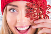 Happy blonde holding red snowflake — Stock Photo