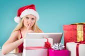 Composite image of festive blonde shopping online with laptop — Stock Photo