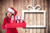 Composite image of festive brunette holding pile of gifts  — Stock Photo