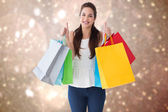 Composite image of happy brunette holding bags with thumbs up — Stock Photo