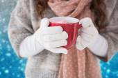 Composite image of woman in winter clothes holding a mug — Foto Stock
