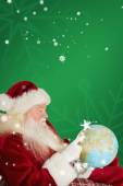 Father christmas pointing to globe — Stock Photo