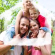 Composite image of happy parents giving their children piggyback — Stock Photo #62470003