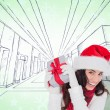 Happy brunette in santa hat holding gift — Stock Photo #62470965