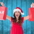 Composite image of brunette showing sale bag and shopping bag — Stock Photo #62472695