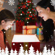 Festive mother and daughter opening a glowing — Stock Photo #62473431