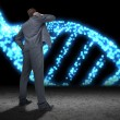 Businessman against blue glittering dna helix — Stock Photo #62473977