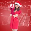 Brunette in santa hat holding gift — Stock Photo #62474375