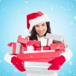 Smiling brunette in santa hat holding stack — Stock Photo #62474463