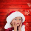 Composite image of cute little girl wearing santa hat and tinsel — Stock Photo #62474661