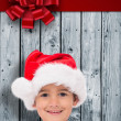 Composite image of cute little boy in santa hat — Stock Photo #62477249