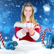 Pretty girl in santa outfit holding gift — Stock Photo #62477481