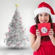 Composite image of festive brunette holding gift with bow  — Stock Photo #62478361