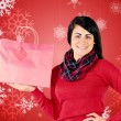 Brunette showing red gift bag — Stock Photo #62479375