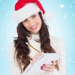 Smiling brunette writing christmas list — Stock Photo #62479943