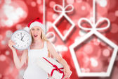 Composite image of festive blonde holding a clock and gift — Photo