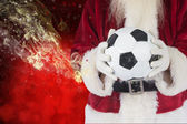 Santa holds a classic football — Stock Photo