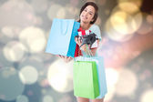 Happy brunette with shopping bags and gifts — Stockfoto