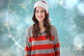 Composite image of beautiful brunette in santa hat smiling at ca — Stock Photo