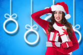Composite image of stressed brunette in santa hat holding gifts — Stockfoto