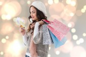 Composite image of happy brunette holding cash and shopping bags — Stock Photo