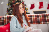 Festive redhead thinking and writing — Stock Photo
