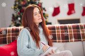 Festive redhead thinking and writing — Foto de Stock