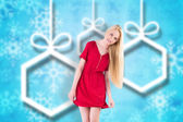 Composite image of pretty blonde in red dress holding skirt — Stock Photo