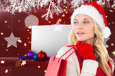 Happy festive blonde with shopping bag — Stock Photo