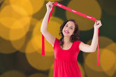 Composite image of stylish brunette in red dress holding scarf  — Stock Photo